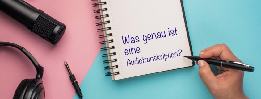 Mikrofon, Kopfhörer, Notizblock und Hand mit einem Stift